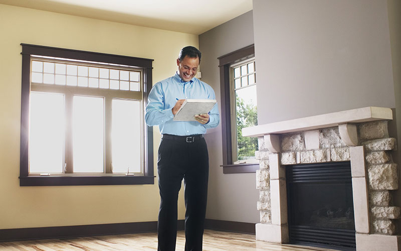 Man writing on clipboard inside home for sale